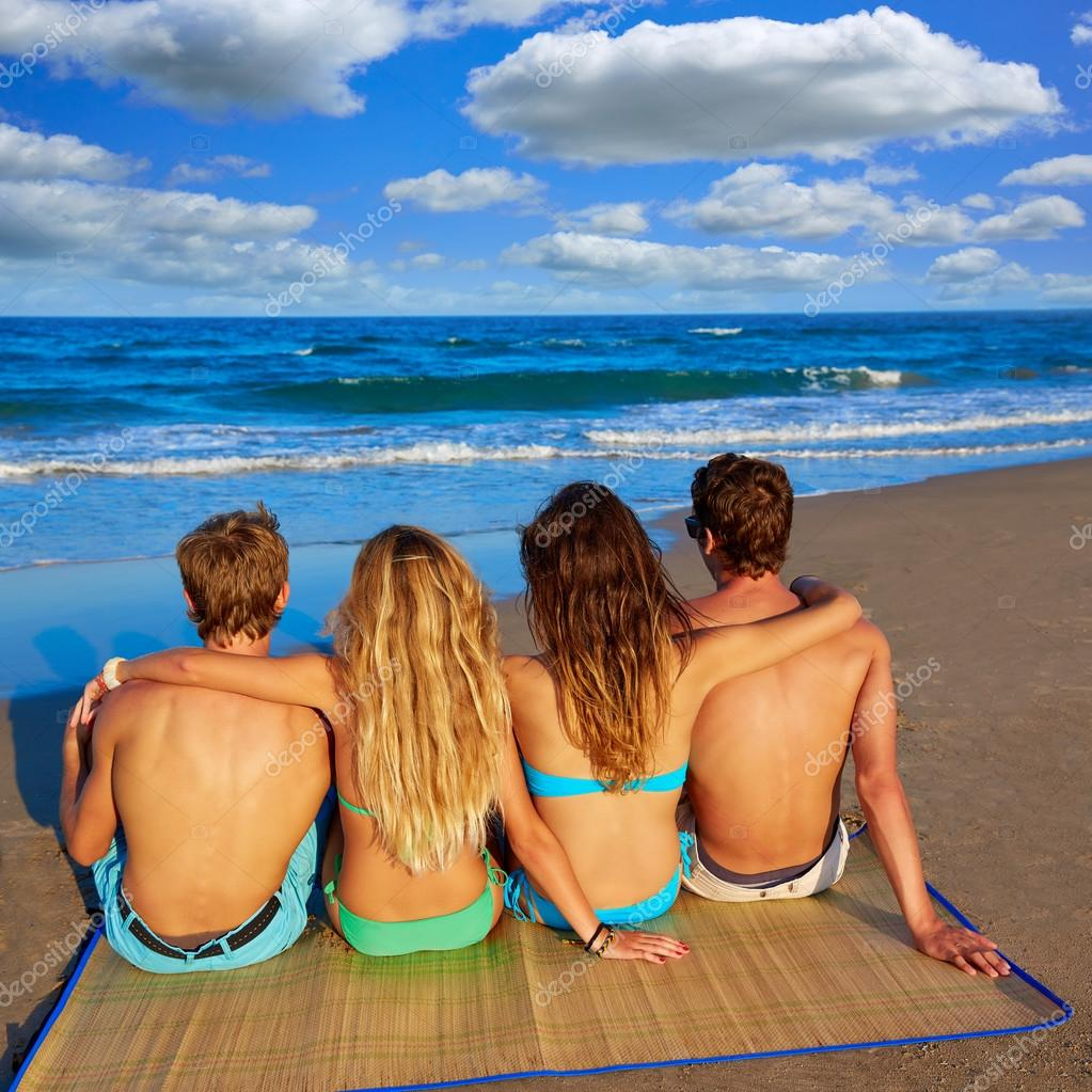 friends group couples sitting in beach sand rear