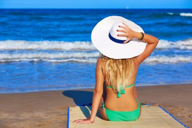 Girl young sitting looking at the sea with beach hat