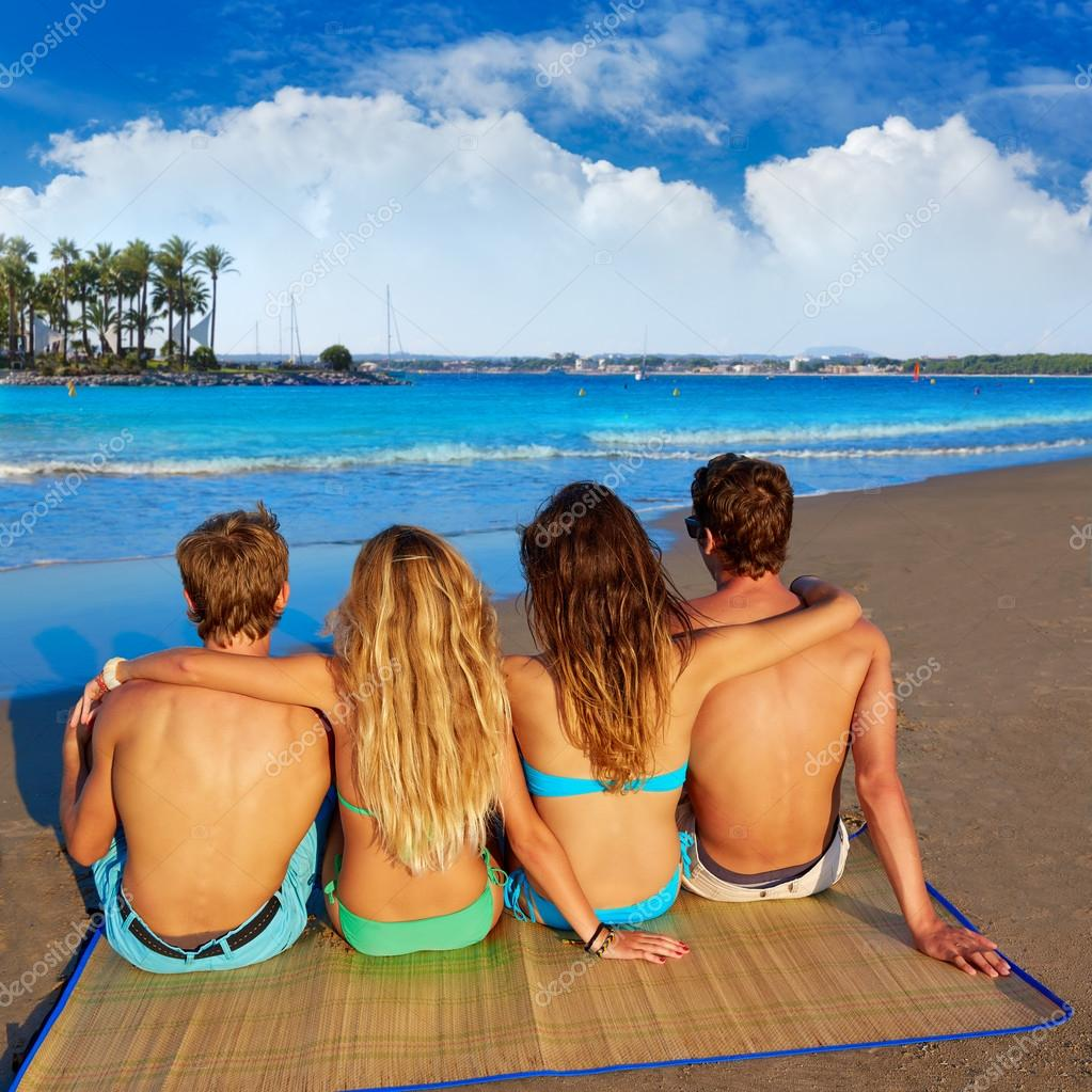 friends group couples sitting beach sand rear view