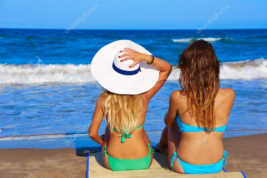 Beach girls rear back biew sitting in the beach