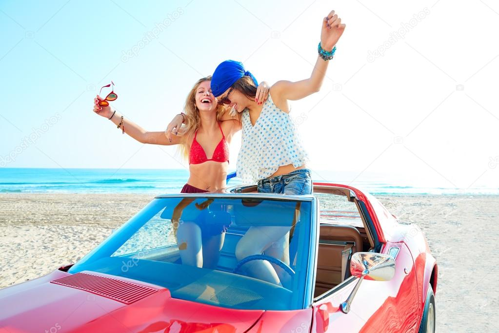 Beautiful party girls dancing in a car on the beach