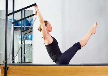 Pilates woman in reformer teaser exercise at gym