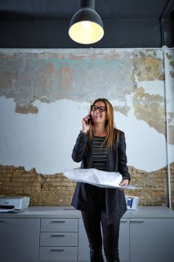Architect woman talking phone holding plan paper