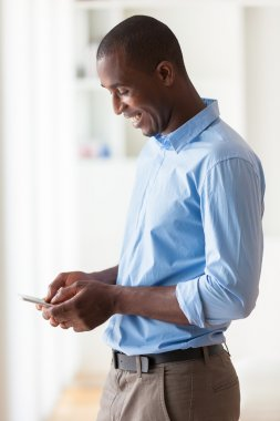 Portrait of a young African American business man using a mobile