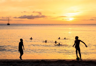 Childrens silhouette playing soccer on sunset at Tarrafal beach