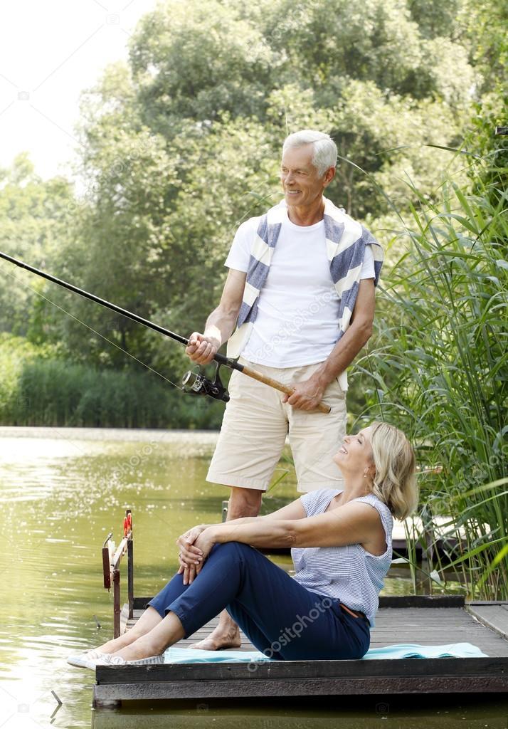 Happy senior couple fishing at lakeshore