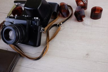 Work space for photographer, designer or hipster style. Have a film camera, film, watch, wallet, knife on wooden table.