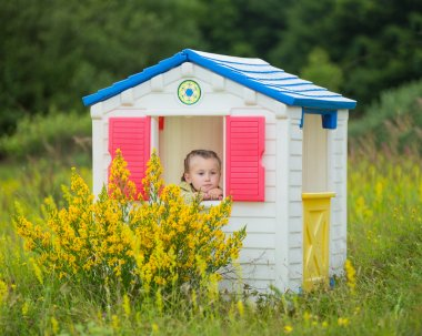 child in a toy house