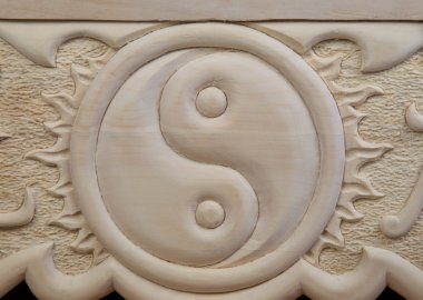 yin yang carved out of wood