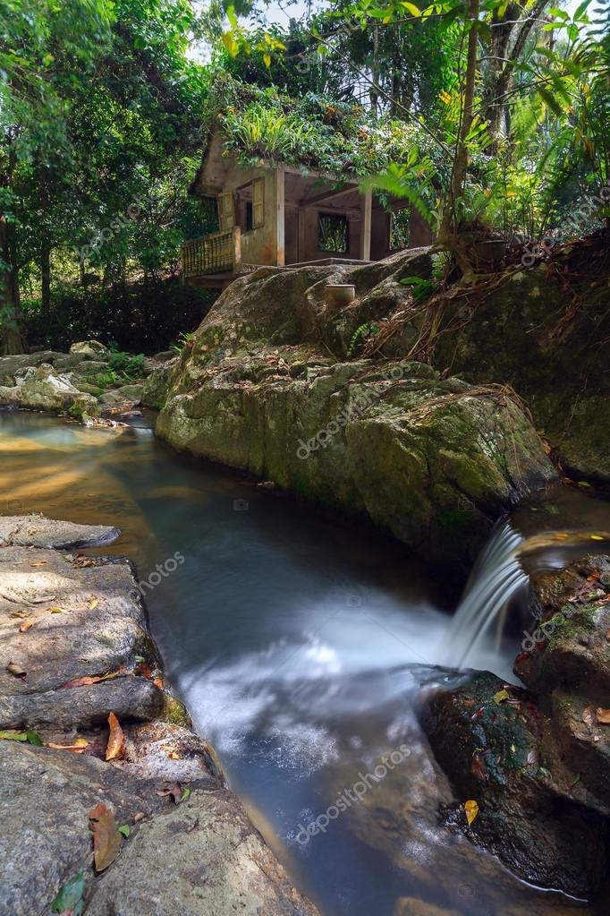waterfall, small river, house in the jungle.
