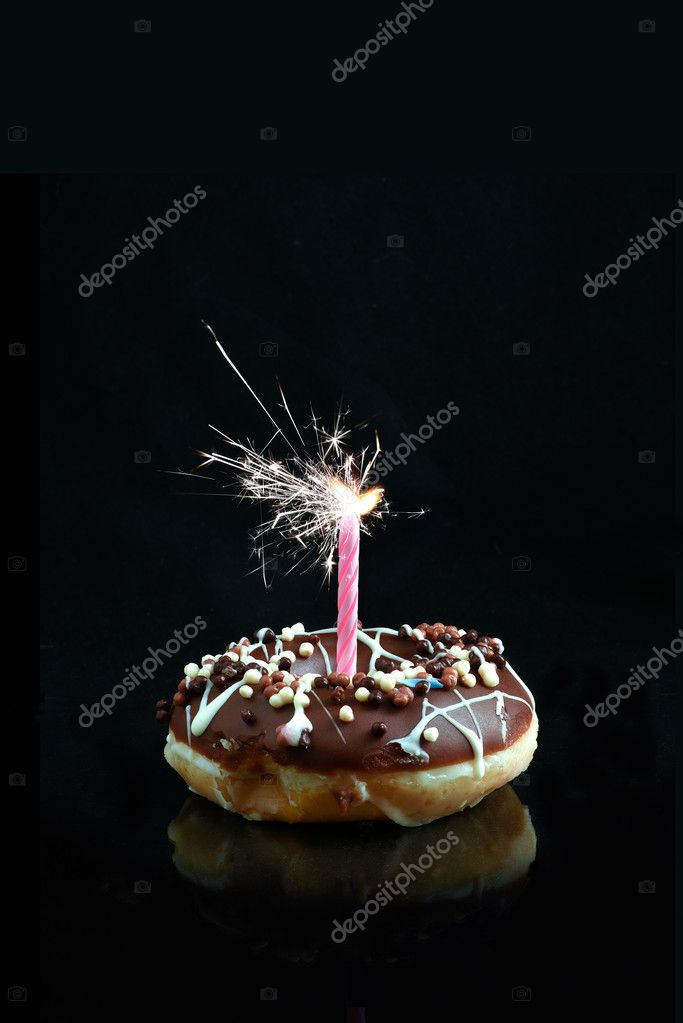 Creative Image Of A Chocolate Smothered Donut With Pink Candle Sparkler Against Black Background Copy Space Concept For Celebrations Or