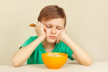 Little discontented boy does not want to eat cereal