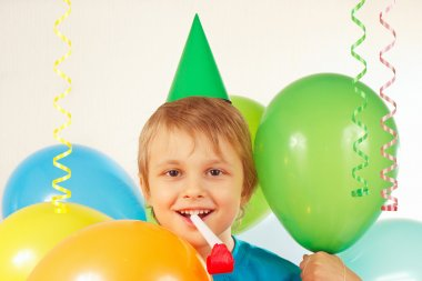 Little blonde boy in holiday cap with whistle and festive balloons and streamer