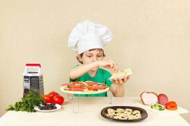 Little boy in chefs hat puts a grated cheese on pizza crust