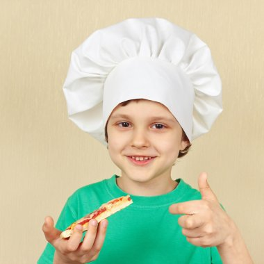 Little smiling boy in chefs hat is going to try cooked pizza