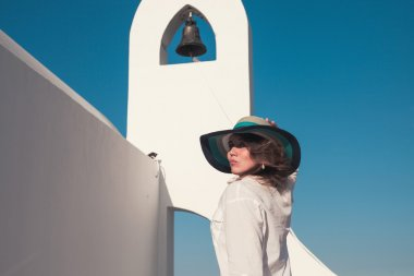 Girl in a hat on a background of a Greek temple bell tower