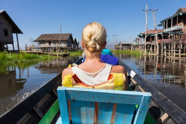 Female tourist travels by traditional boat.