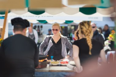 Beautiful blonde caucasian lady buying freshly prepared meal at a local street food festival. Urban international kitchen event in Ljubljana, Slovenia, in summertime. stock vector
