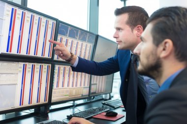 Businessmen trading stocks. Stock traders looking at graphs, indexes and numbers on multiple computer screens. Colleagues in discussion in traders office. stock vector