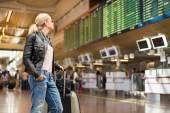 Photo Female traveller checking flight departures board.