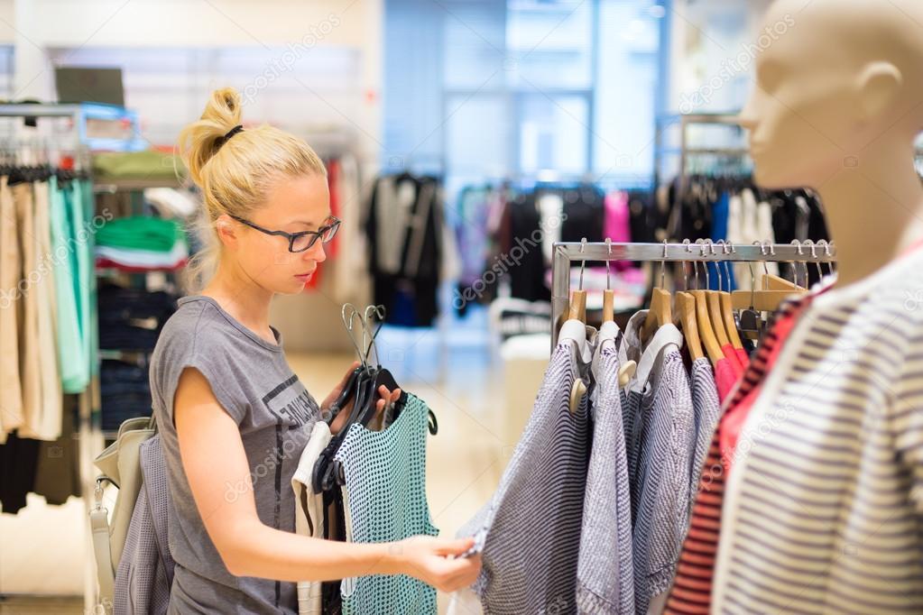 06ac4e52b Compras de roupas de mulher. cliente à procura de roupa dentro de casa na  loja. bela loiro caucasiano feminino modelo vestindo preto glases.