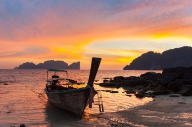 Traditional wooden longtail boat on beach in sunset, Thailand.