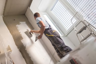 Plasterer renovating indoor walls and ceilings.
