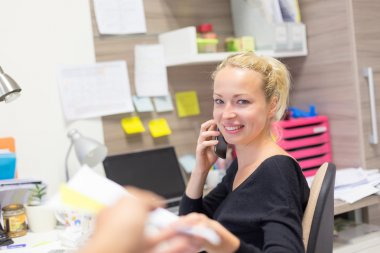 Businesswoman talking on mobile phone in office.