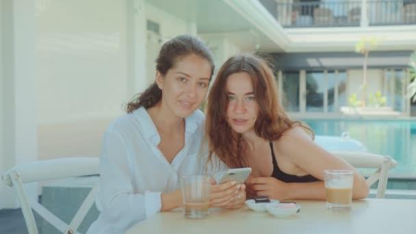 Dvě mladé atraktivní ženy pijí kávu v restauraci a dívají se na telefon
