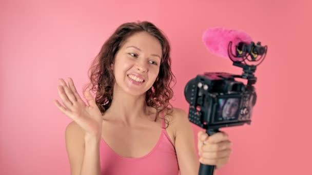 Junge Frau vlogger Aufnahme ausgestrahlt in Zeitlupe auf rosa Hintergrund