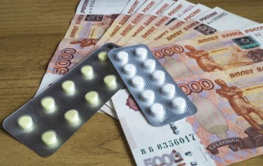 Money bills with medical tablet