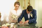 Closeup of young groom signing wedding contract at registry offi