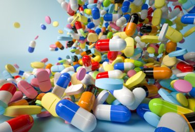 Many colorful pills and capsules falling on white background