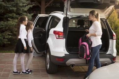 Mother meets daughters after school and putting their bags in th