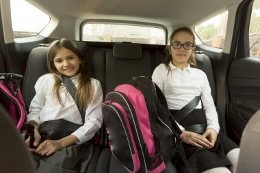 Portrait of cheerful schoolgirls sitting on car back seat