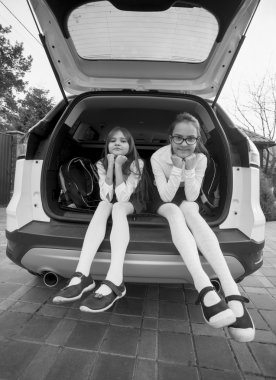 Black and white photo of two schoolgirls sitting in open car tru
