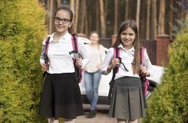 Two girls posing with school bags after lesson in school