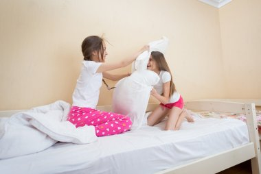 Two teenage girls in pajamas having fun and fighting with pillow