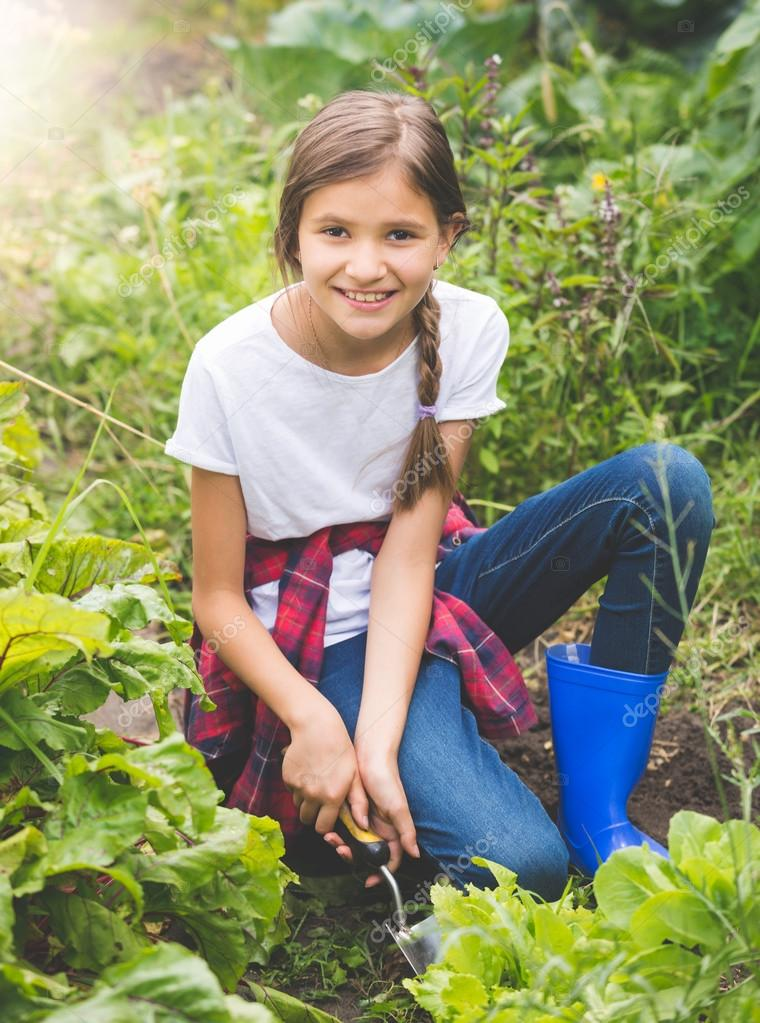 Happy smiling teenage girl planting lettuce at garden at sunny d