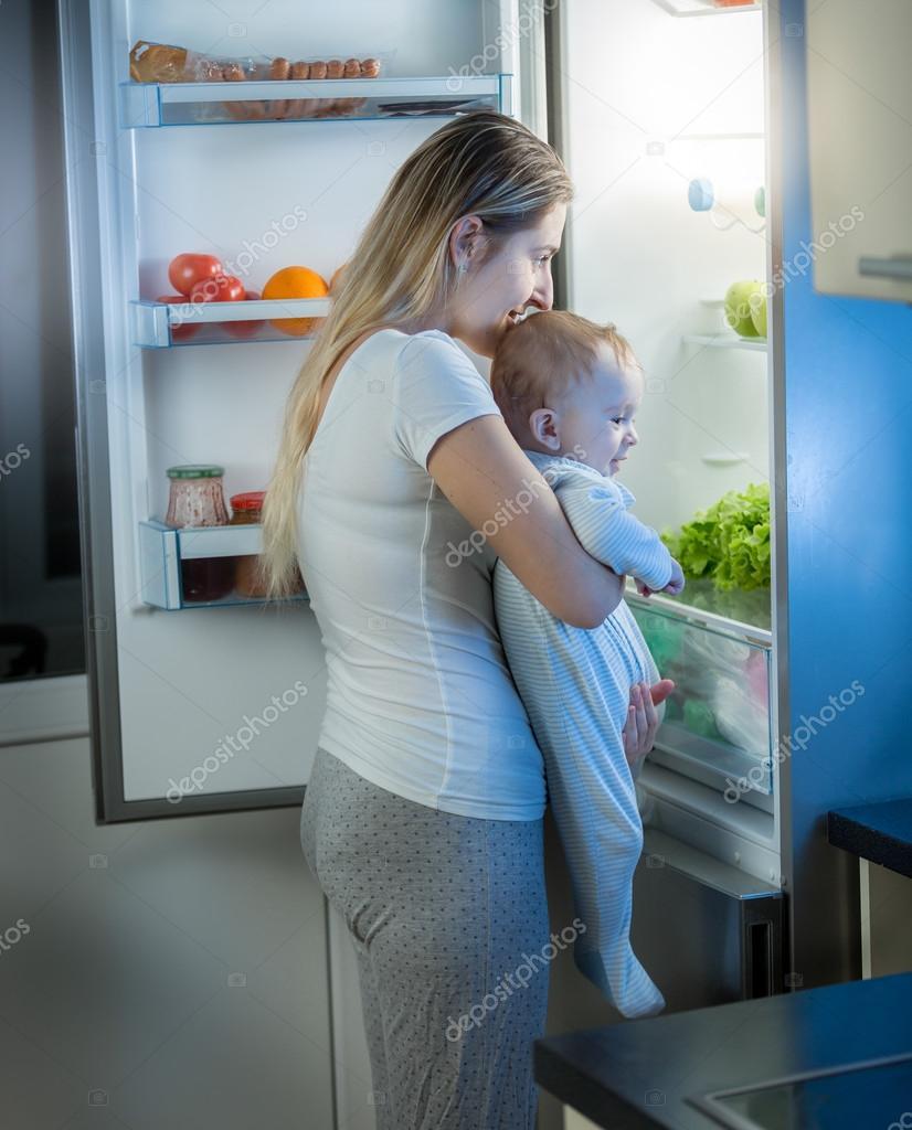 Junge Mutter hält Baby Sohn und suchen innerhalb der Kühlschrank ...