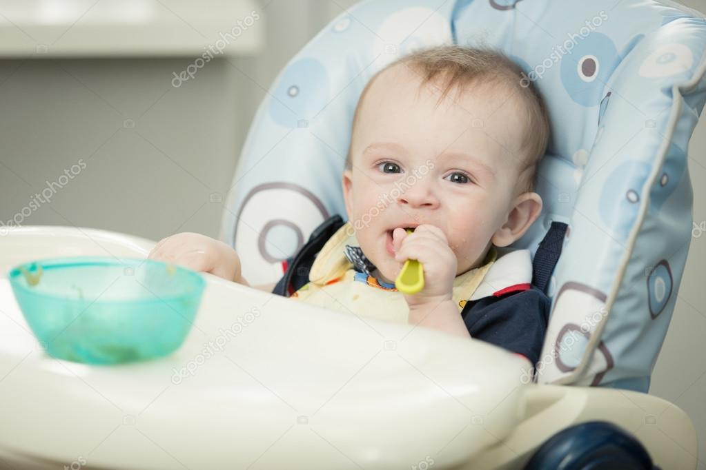 553949374d9 Πορτρέτο του αξιολάτρευτο 9 μηνών αγόρι τρώει στο καρεκλάκι στο κιτ — Φωτογραφία  Αρχείου