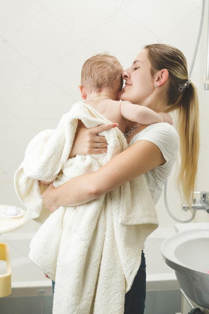 young mother kissing her baby at bathroom after having bath stock photo 123410220