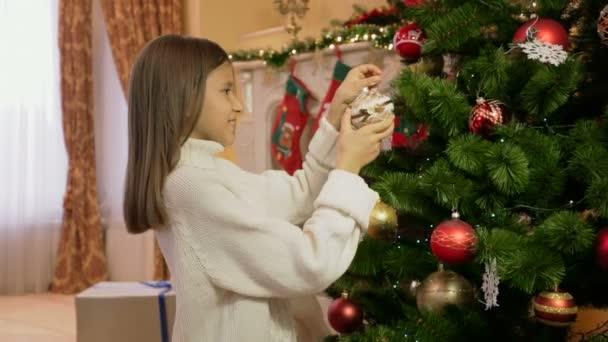 Porträt von netten Mädchen in weißen Pullover schmücken Weihnachtsbaum