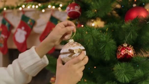Detailní záběr mladá žena zdobení vánočního stromu s cetky