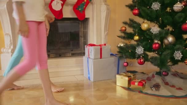 Dvě dívky v pyžamu a v obývacím pokoji a užívat vánoční dárky