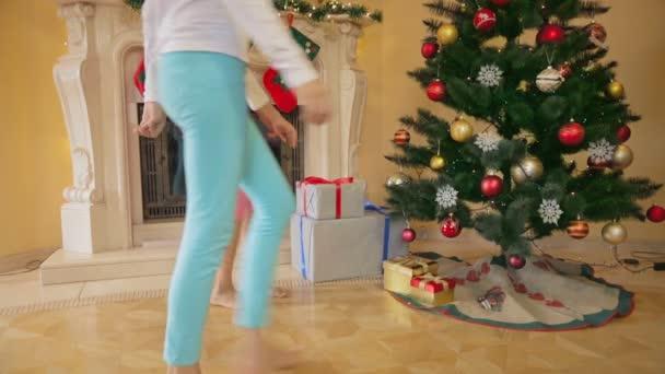 Dvě dívky v pyžamu s vánoční dárky a jejich otevření