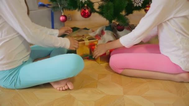 Nahaufnahme von zwei süßen Schwester öffnet Weihnachtsgeschenke am Morgen