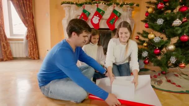 Glückliche Familie sitzt am Boden und die Verpackung Weihnachten präsentiert in Papier und mit Bändern dekorieren