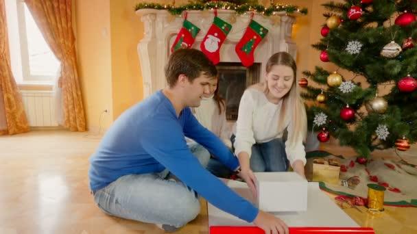 Fiatal boldog családi összejövetel, a nappali és a karácsonyi ajándékok csomagoló papír