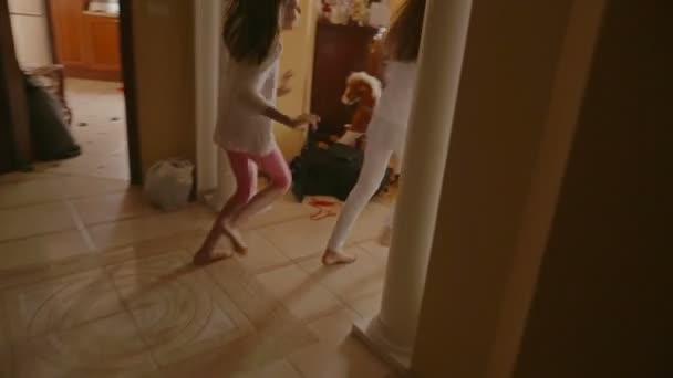 Két vidám lány fut a karácsonyfa alatt ajándékok: reggel